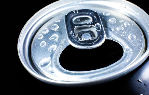 黒の背景にドロップと炭酸飲料の缶。夏の暑さの中でさわやか。休暇の気分。