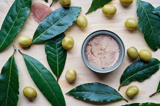 올리브와 베이 잎으로 둘러싸인 참치 평면도의 캔