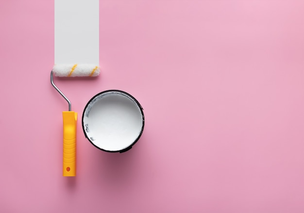 コピースペースのあるピンクの背景に白いペンキと白いペンキのストリップが付いたローラーの缶。