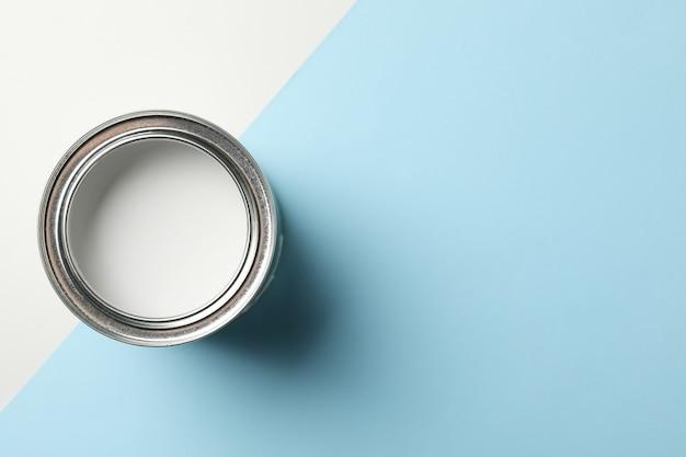 Банка белой краской на двухцветной поверхности