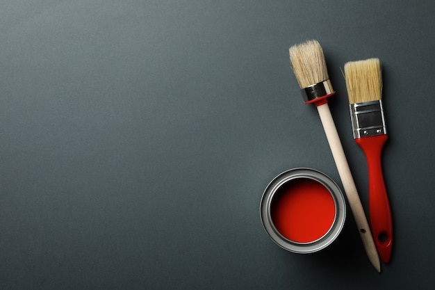 Can of red paint and brushes on black background, top view