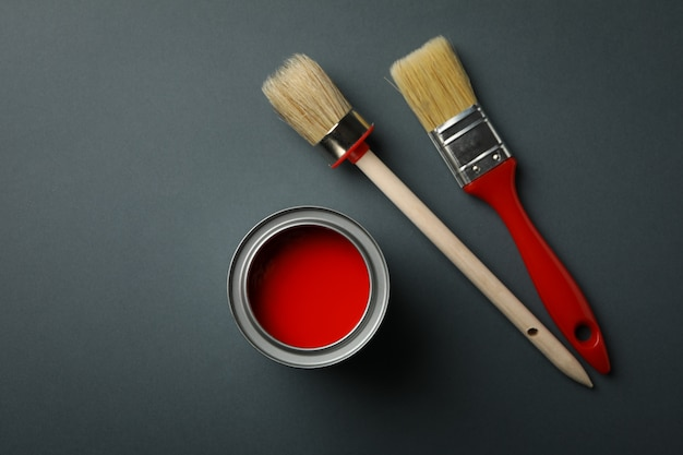 Can of red paint and brushes on black surface