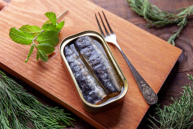 Can of sardines in oil on kitchen board