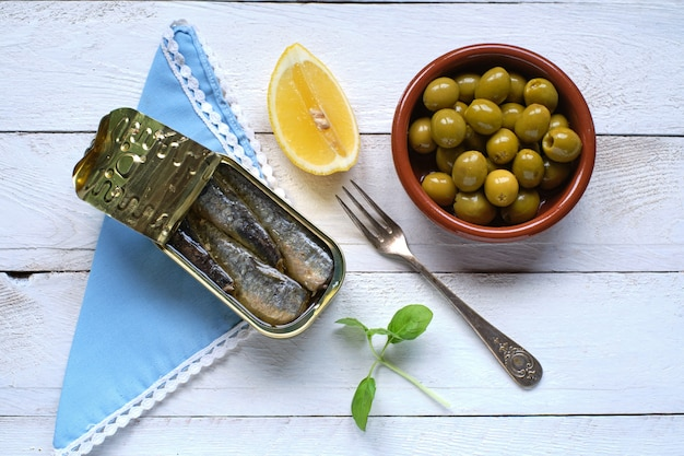 Can of sardines in oil, olive and lemon from above on white rustic table