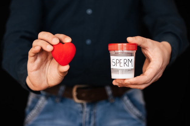 Can of sperm and a red heart in a man's hands