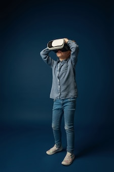 Can't believe her eyes. little girl or child in jeans and shirt with virtual reality headset glasses isolated on blue studio background. concept of cutting edge technology, video games, innovation.