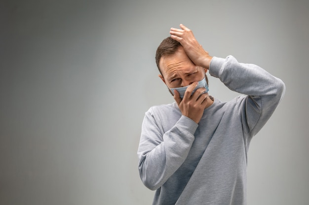 Can't breathe. caucasian man wearing the respiratory protection mask against air pollution and dust particles exceed the safety limits. healthcare, environmental, ecology concept. allergy, headache.