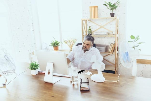 집중할 수 없습니다. 사업가, 컴퓨터와 팬이 있는 사무실의 관리자, 더위를 식히고 있습니다. 팬을 사용하지만 여전히 캐비닛의 불편한 기후로 고통 받고 있습니다. 여름, 사무실 작업, 비즈니스.