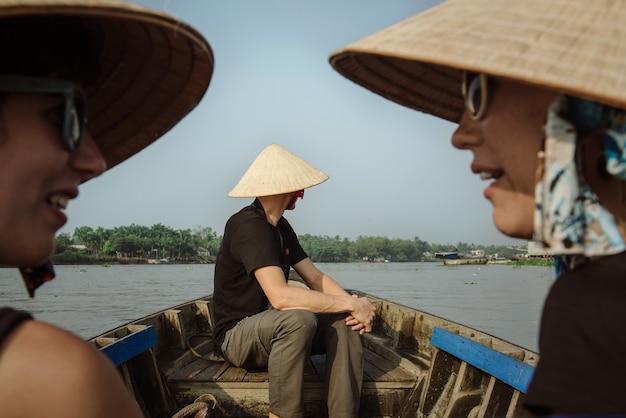 カントー、ベトナム-2016年4月2日:ボートでメコンデルタに旅行に行くベトナムの帽子の観光客。人気の観光地である水上マーケットカイランに行く観光客のグループ