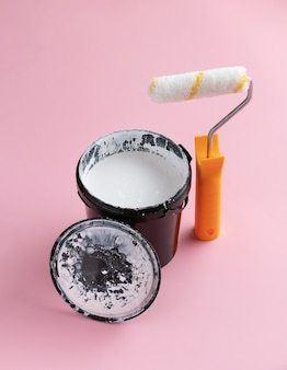Can of white paint and a roller. creative home renovation concept.