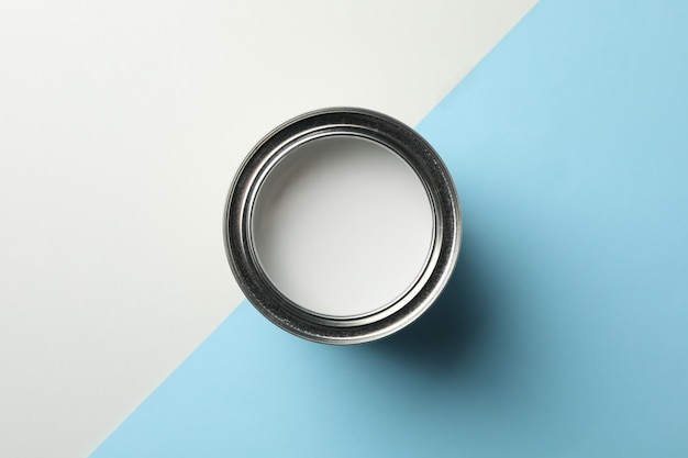Can of white paint on two tone background, top view