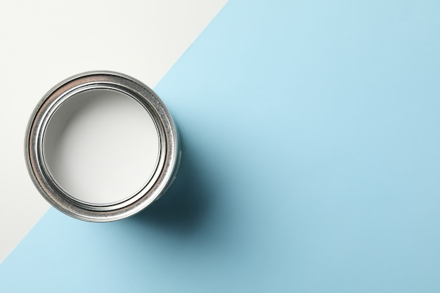 Can of white paint on two tone surface