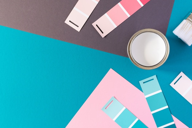 Can of white paint with brush on colorful background, selection of palette for painting, sample color catalog, top view