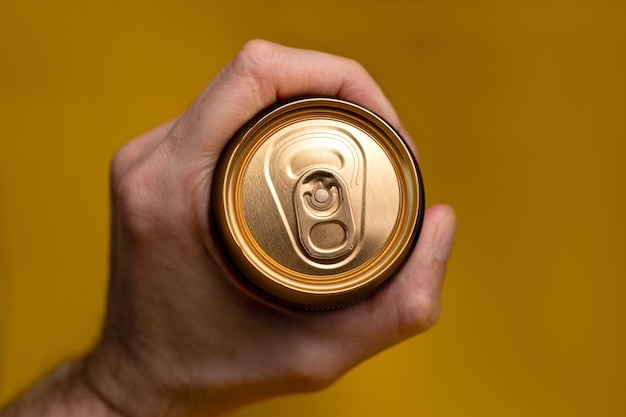 A can with a drink in a man's hand.