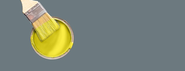 Can with paint of illuminating yellow color and paintbrush on ultimate gray background. color of the year 2021