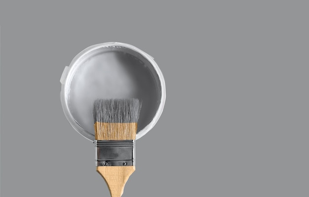 Can with paint of ultimate gray color and paintbrush. color of the year 2021