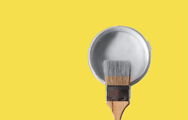Can with paint of ultimate gray color and paintbrush on illuminating yellow background. color of the year 2021