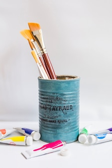 Can with paintbrushes on white
