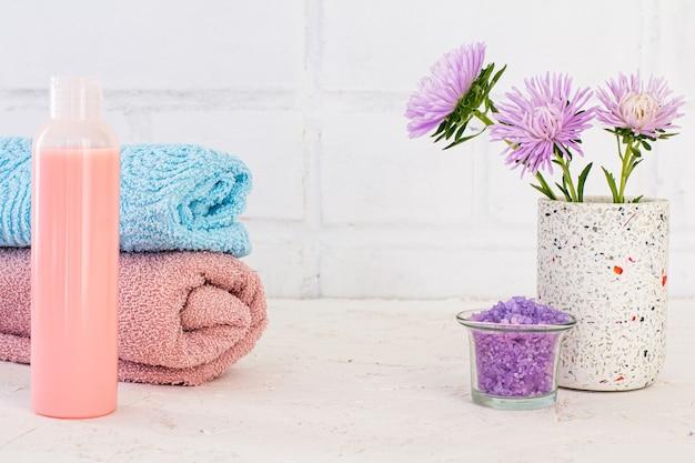 Банка с морской солью, бутылка шампуня, полотенца и цветы астры на белом фоне.