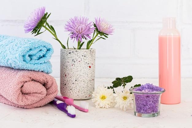 Банка с морской солью, бутылка шампуня, полотенца, зубные щетки и цветы астры на белом фоне