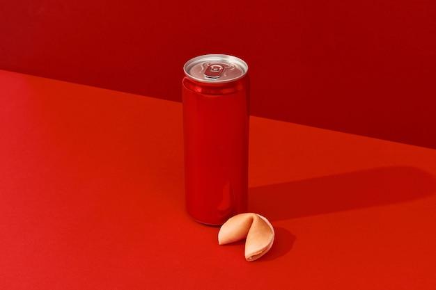 햇빛 아래 빨간색 배경에 청량 음료와 포춘 쿠키가 있는 캔