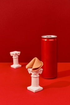 Can with soft drink and fortune cookies on a red background in sunlight