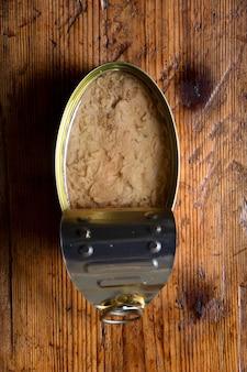 나무 배경에 기름을 얹은 참치 캔