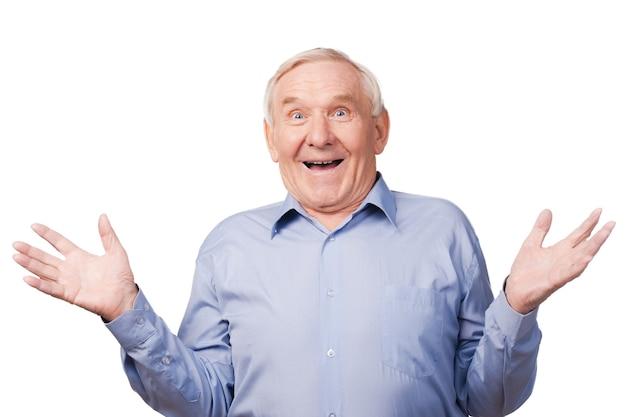 Ты можешь в это поверить! возбужденный старший мужчина жестикулирует и улыбается, стоя на белом фоне