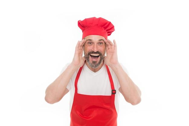 私の声が聞こえますか。シェフの帽子とエプロンでひげを生やした成熟した男。よだれかけのエプロンを身に着けているひげと口ひげを生やした上級料理人。赤い調理エプロンで成熟したチーフクック。家庭料理。