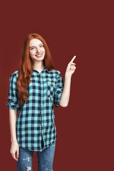 あなたはそれが赤い背景に立っている指で指している赤毛の笑顔の女の子を見ることができます