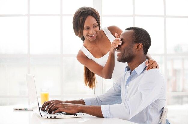그만 일해도 돼? 노트북에서 일하는 동안 남자친구의 눈을 가리고 있는 아름다운 젊은 아프리카 여성