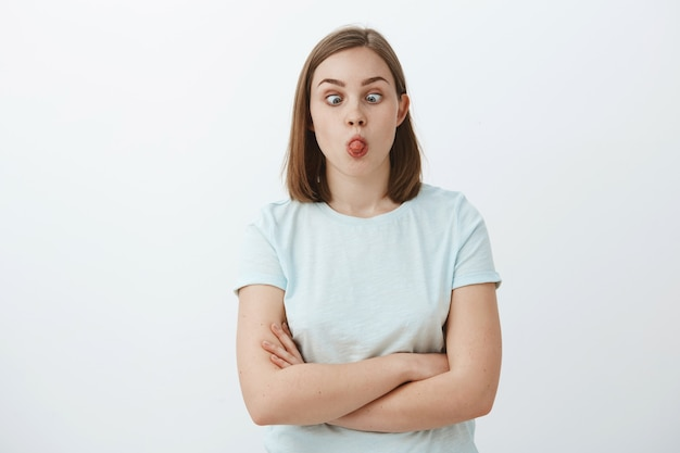 Can you touch nose with tongue. portrait of funny playful and immature cute woman with short brown hair squinting eyes making faces and fooling around having fun over grey wall