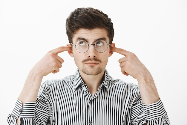 Can you turn off music please, i am studying. calm displeased nerdy male student in nerd glasses and striped shirt, covering ears with index fingers, looking up, being bothered from loud noise
