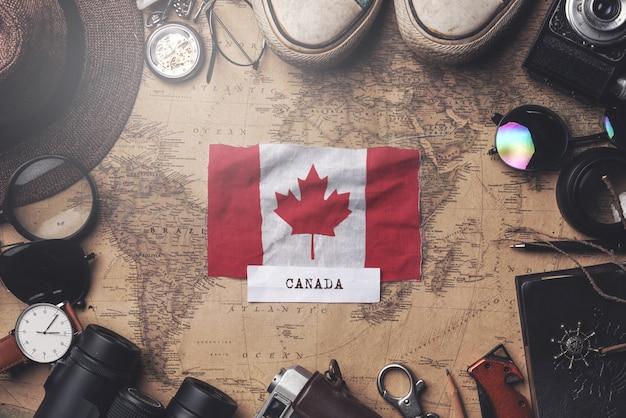 古いビンテージマップ上の旅行者のアクセサリー間のカナダの国旗。オーバーヘッドショット