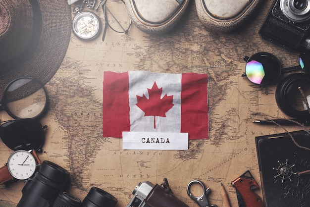 Canada flag between traveler's accessories on old vintage map. overhead shot