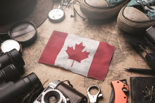 Canada flag between traveler's accessories on old vintage map. tourist destination concept.