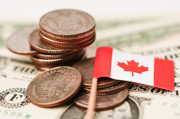 Canada flag with coins on dollar banknotes background.