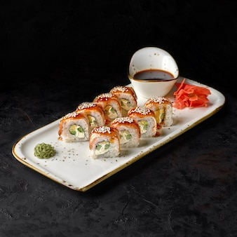 Canada roll with eel, cheese cream and cucumber placed on a black textured background