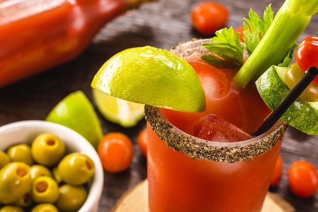 Канадский напиток цезарь. сделано с водкой, острым соусом и вустерширским соусом, украшено стеблем сельдерея и долькой лимона.