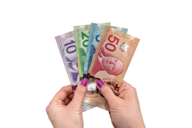 Canadian dollar on female hand isolated on white