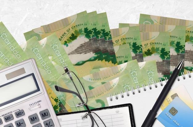 Счета канадских долларов и калькулятор с очками и ручкой