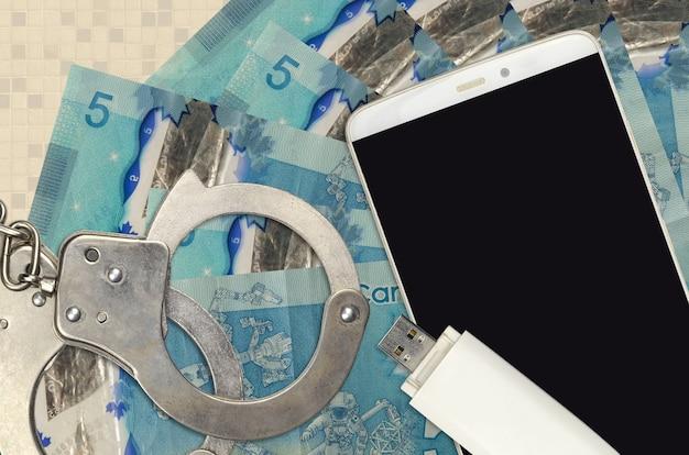 Купюры канадских долларов и смартфон с полицейскими наручниками