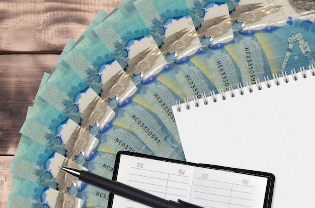 Вентилятор банкнот канадских долларов и блокнот с контактной книгой и черной ручкой