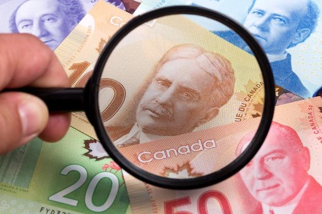 Канадские доллары на фоне увеличительного стекла