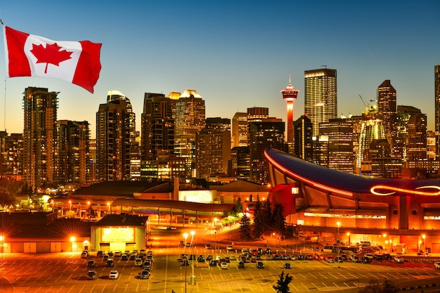 Canadian flag in calgary city skyline at twilight time, alberta