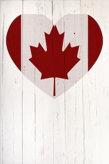 Canadian flag in heart shape on a white wooden board