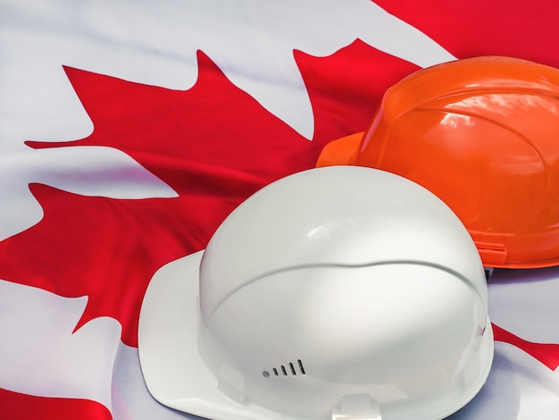 Canadian flag and two protective hardhats. close-up