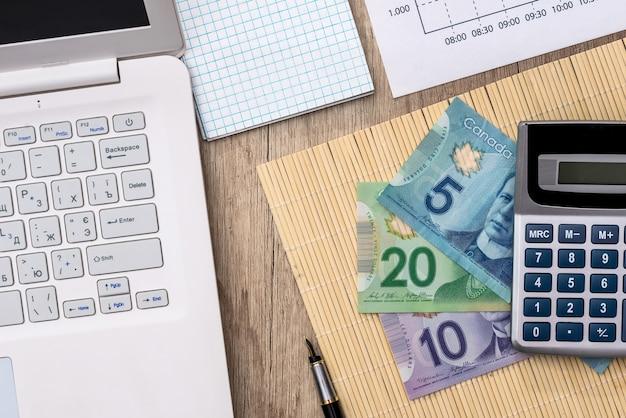 Канадские деньги с ноутбуком, документом, кастрюлей и калькулятором