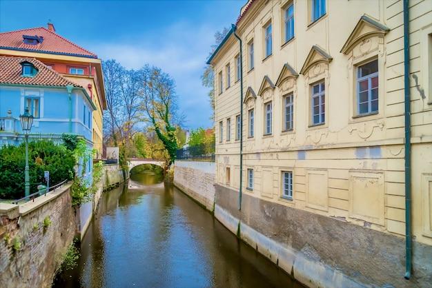 チェコ、プラハ、マラーストラナのレノンの壁近くの建物の間を流れる運河