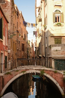 Canal in italian venice between ancient buildings with boats on it. and a pedestrian bridge across this bridge.